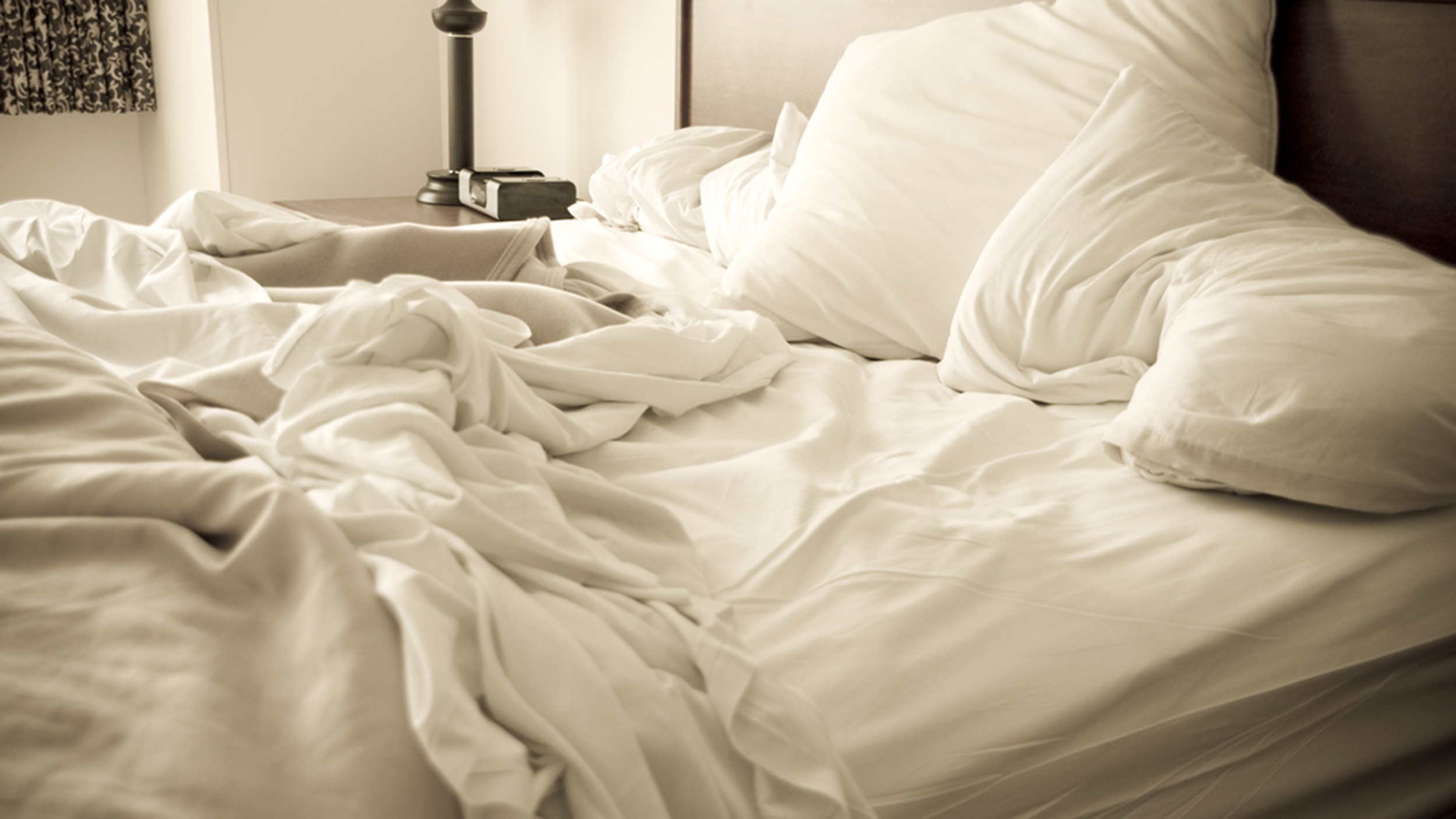 An unmade bed with white linens and a lamp in the corner.; Shutterstock ID 197136716; PO: MC for TODAY