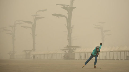 BEIJING, CHINA - DECEMBER 01:  A woman wearing a mask practices roller blading at Olympic Park during dheavy smog on December 1, 2015 in Beijing, China. The representatives of the governments of more than 190 countries are meeting in Paris this week, including Chinese President Xi Jinping will attend the Paris meeting.  (Photo by Feng Li/Getty Images)