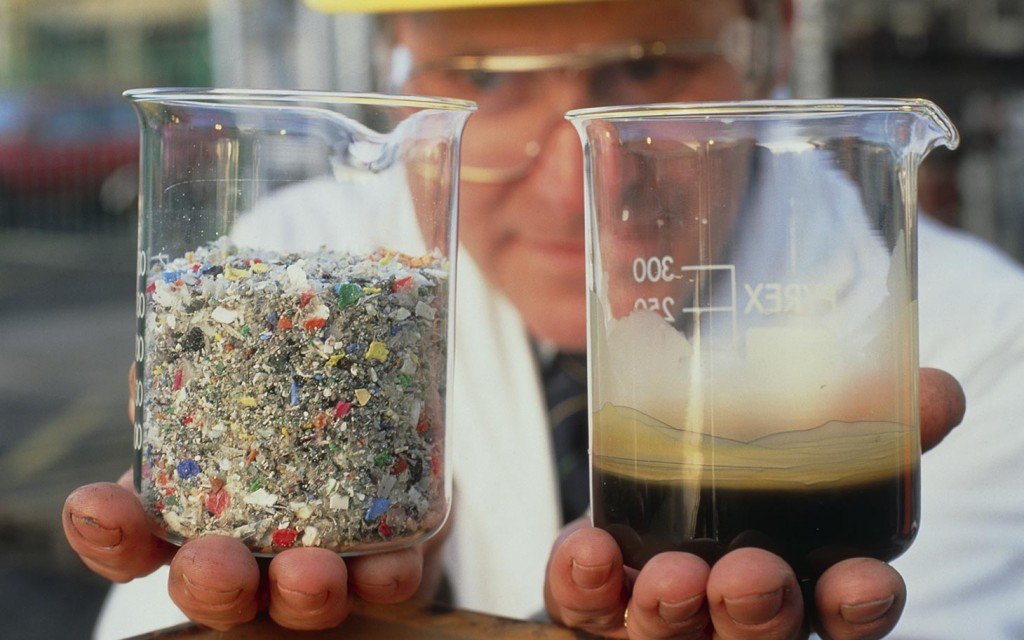 Plastics recycling. Chemical engineer David Wilson holding a sample of waste plastic (left) and an oil feedstock reclaimed from it at BP's Feedstock Recycling Pilot Plant at Grangemouth, Scotland. The waste plastic is first cleaned and shredded. It is then passed through a fluidized bed of sand at over 400 degrees Celsius, breaking the long molecules in the plastic down into smaller, basic hydrocarbons. The hydrocarbons, in gaseous form, are filtered and condensed to produce this pure, waxy substance. This may be used as a primary feedstock for refineries or the petrochemical industry. Waste heat is itself recycled in the system, giving an energy efficiency of 85%-90%.