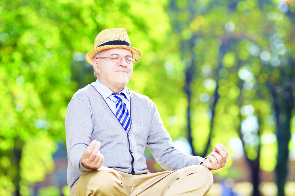 Senior gentleman meditating in a park