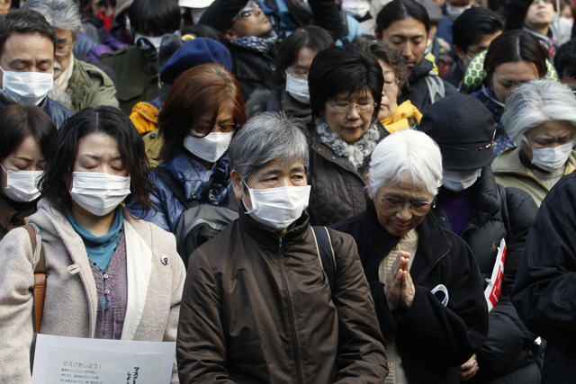 Anti-nuclear protesters take part in a moment of silence at 2:46 p.m. (0546 GMT) during a rally in Tokyo March 11, 2012, to mark the first anniversary of the earthquake and tsunami that killed thousands and set off a nuclear crisis. With a moment of silence, prayers and anti-nuclear rallies, Japan marked on Sunday one year since an earthquake and tsunami killed thousands and set off a radiation crisis that shattered public trust in atomic power and the nation's leaders. REUTERS/Stringer (JAPAN - Tags: ANNIVERSARY DISASTER POLITICS CIVIL UNREST)
