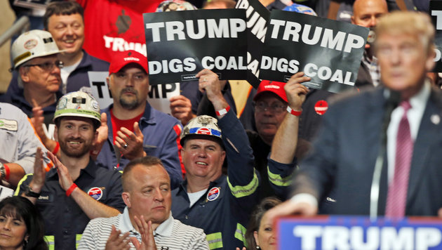 Coal miners wave signs as Republican presidential candidate Donald Trump speaks during a rally in Charleston, W.Va., Thursday, May 5, 2016. (AP Photo/Steve Helber)