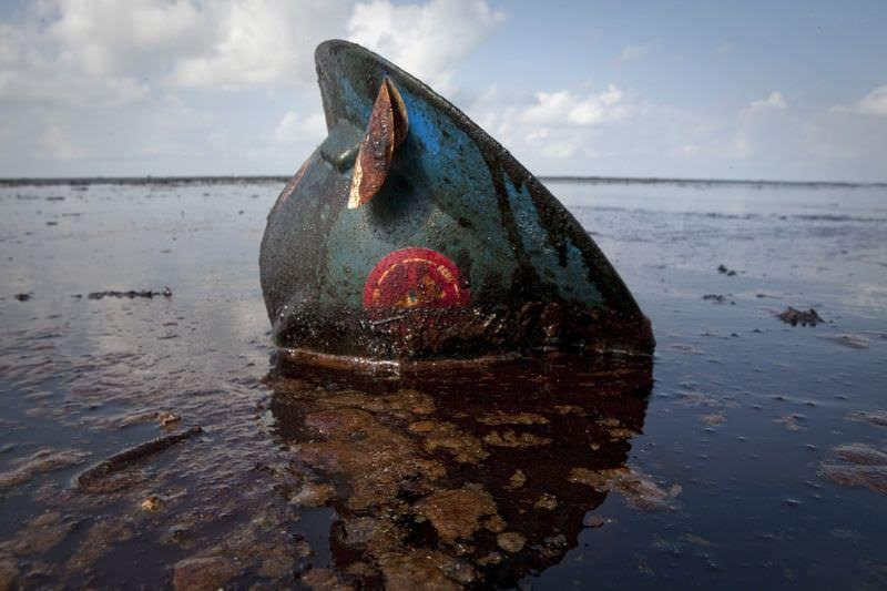 A hard hat from an oil worker lies in oil from the Deepwater Horizon gulf oil spill on East Grand Terre Island, Louisiana in this June 8, 2010 file photo. When BP's Deepwater Horizon oil rig exploded and sank in the Gulf of Mexico last April, killing 11 workers, authorities first reported that no crude was leaking into the ocean. They were wrong. One year on, oil from the largest spill in U.S. history clogs wetlands, pollutes the ocean and endangers wildlife, not to mention the toll it has inflicted on the coastal economies of Florida, Mississippi, Alabama and especially Louisiana. REUTERS/Lee Celano/Files (UNITED STATES - Tags: ANNIVERSARY BUSINESS DISASTER ENERGY ENVIRONMENT)